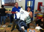 Alan Young passes out Marlins Ayudan t-shirts.