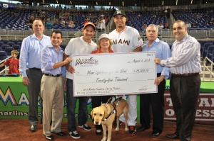 The Miami Marlins and the Marlins Foundation present Miami Lighthouse for the Blind and Visually Impaired with a check for $25,000.